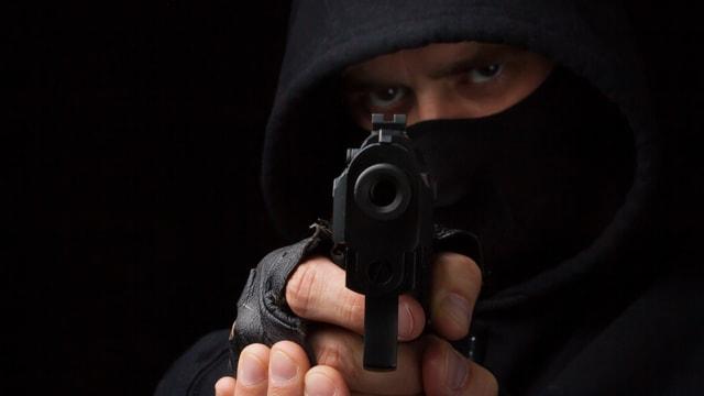 Ein Mann zielt mit einer Pistole auf die Kamera