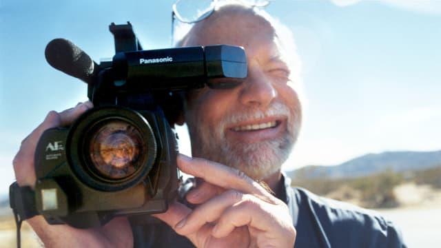 Ein Mann blickt mit einer Filmkamera in die Kamera.