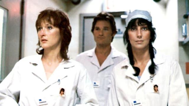 Filmszene: Meryl Streep, Kurt Russell und Cher in weissen Arbeitsanzügen