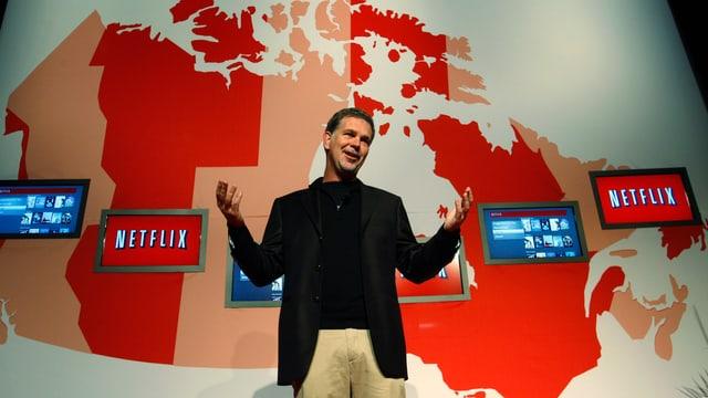 Netflix-CEO Reed Hastings steht vor einer Karte der USA.