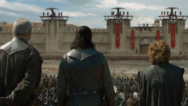 Drei Männer vor einer Stadtmauer.