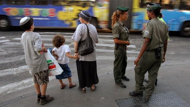 Orthodoxe Jüdin mit zwei Kindern mit Kippa am Strassenrand vor einer Krezung, daneben drei Polizisten, davon eine Polizistin.