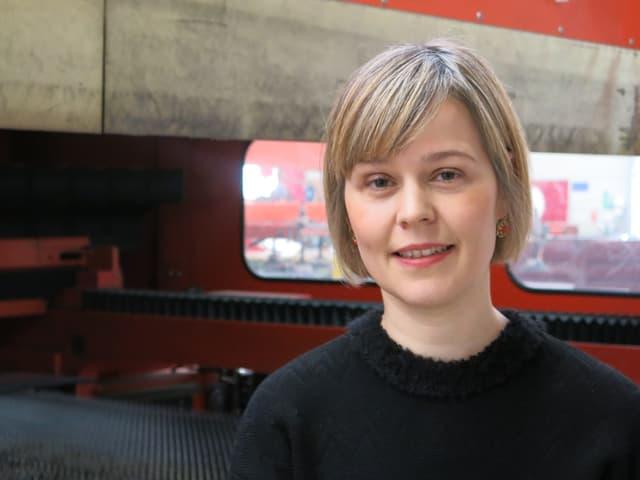 Anna Aebischer in der Produktionshalle vor einer Lasermachine.