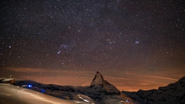 Ein Sternenhimmel hoch über Zermatt und dem Matterhorn. Abertausende kleine Punke leuchten.
