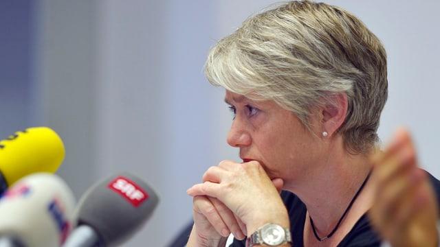Ein Frau mit kurzen, grauen Haaren stütz den Kopf auf die Hände.