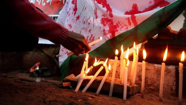 Demonstranten zünden Kerzen für das Opfer an.