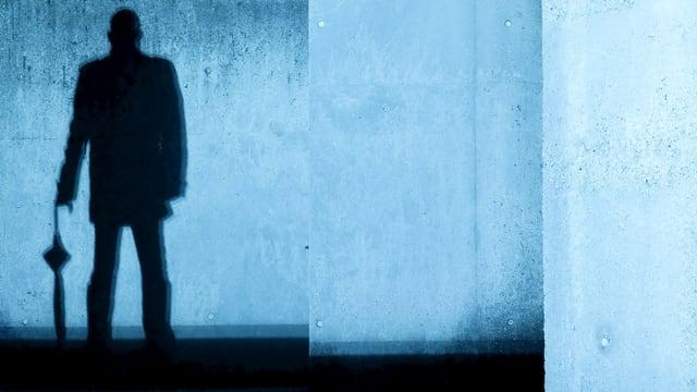 Ein Mann mit Regenschirm wirft einen Schatten an die Wand.