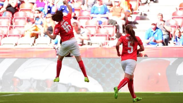 Die Schweizer Nati-Spielerin Fabienne Humm mit der Nummer 16 auf dem roten Trikot springt am FIFA World Cup 2015 vor der Zuschauertribüne in die Luft, rechts daneben Teamkollegin Noëlle Maritz mit der Nummer 5.