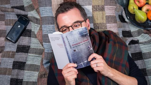 Ein Mann liegt auf einer Decke und liest.