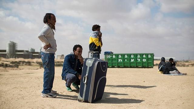 Männer stehen und sitzen in der Wüste, neben ihnen ein grosser Reisekoffer.