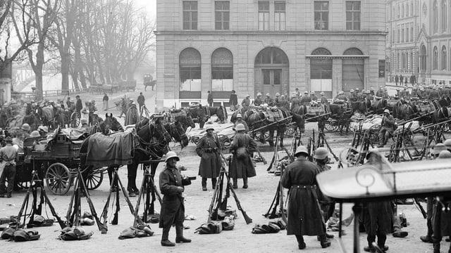 Auf einem Platz stehen Soldaten mit Helm, aufgetürmte Gewehre und Pferdekutschen.