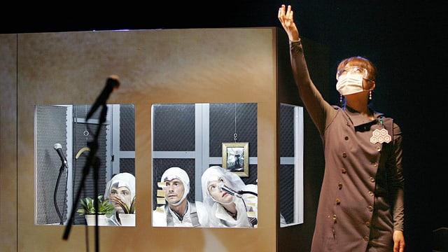 Drei Schauspieler in weissen Kleider sitzen in einer Kabine, davor ein Mikrofon, daneben eine vierte Schauspielerin, die ihren Arm nach oben reckt.