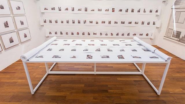 In einem Raum liegen auf einem Tisch eine Vielzahl von Architektur-Bildern, ebenso hängen solche an den Wändern drum herum.