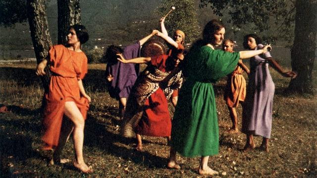 Sieben Frauen in weiten, farbigen Kleidern, tanzen im Wald