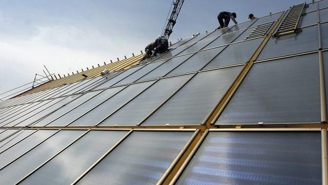 Arbeiter montieren auf einem steilen Dach Solarzellen.
