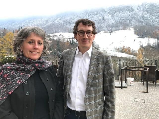 Eine Frau und ein Mann in Winterkleidung stehen vor einer verschneiten Landschaft.