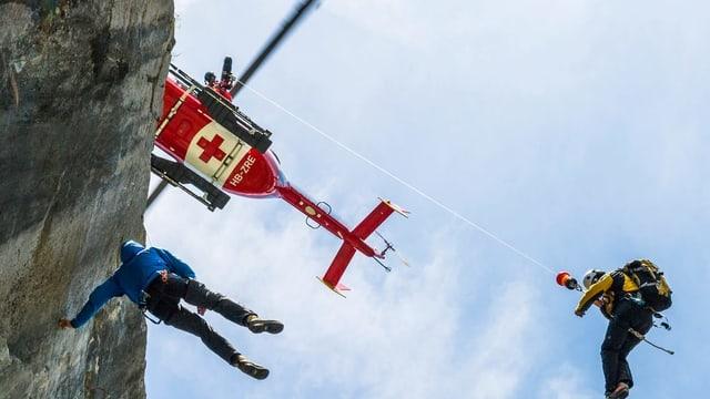 In herlicopter da salvament cun duas persunas. Exercizi da salvament vi d'in grip.