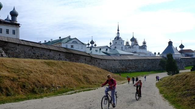 Kinder fahren auf Fahrrädern am Kloster vorbei.