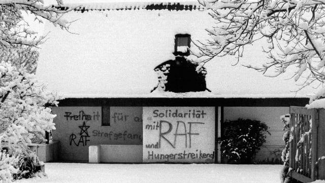 Ein Haus mit schneebedecktem Dach. Auf die Wände wurden Sprüche wie «Solildarität und Hungerstreik mit RAF» gesprayt.