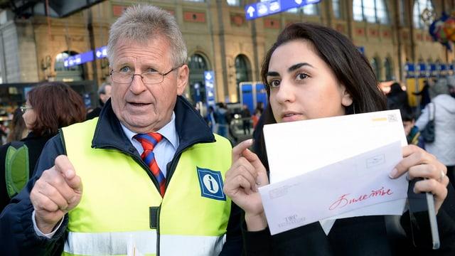 Ein Mann mit einer gelben Weste, daneben eine Frau mit einem Papier in der Hand.