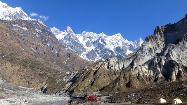 Ein Hubschrauber und zwei Zelte vor einer mächtigen, aber gletscherlosen Bergkulisse im Himalaja.