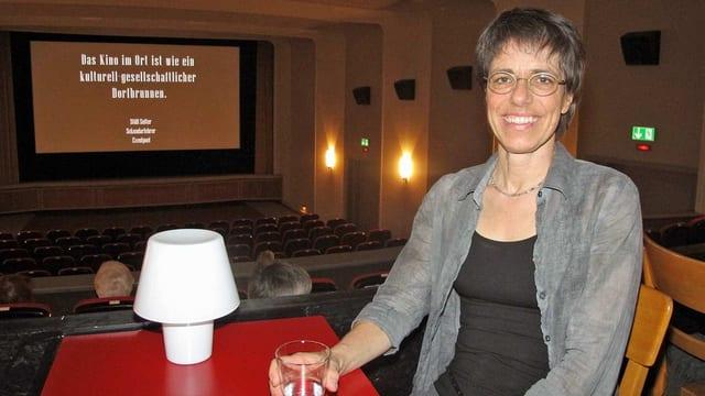 Eine Frau mit kurzen, grauen Haar sitzt vor der Kinoleinwand.