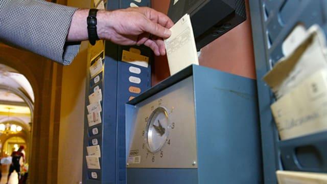 Ein Mann steckt eine Karte in eine Stempeluhr.