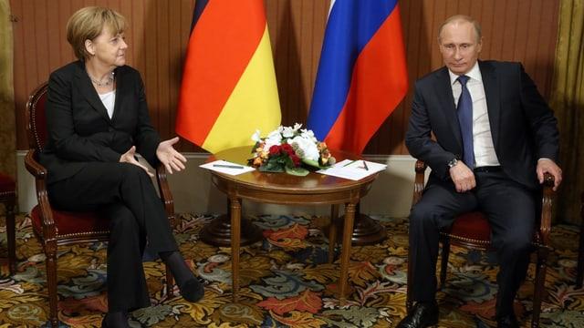 Angela Merkel (l.) sitzt neben Wladimir Putin vor Fahnen von Deutschland und Russland