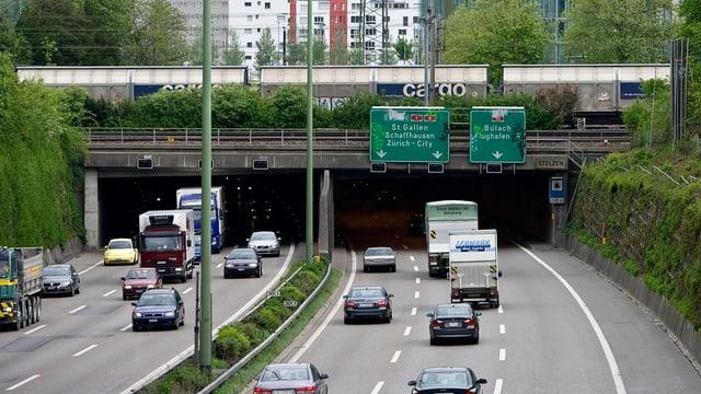 Bahnbrücke mit Zug über der Autobahn.