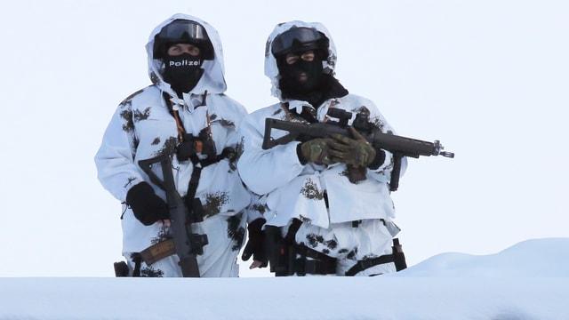 Soldaten mit Waffe und in weisser Tarnkleidung beobachten Davos.