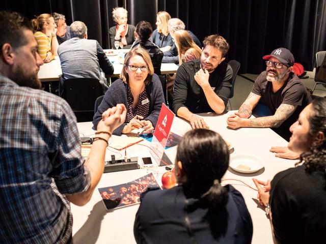 Teilnehmerinnen und Teilnehmer des SRF Familien-Forums bei einem Workshop an einem Tisch.