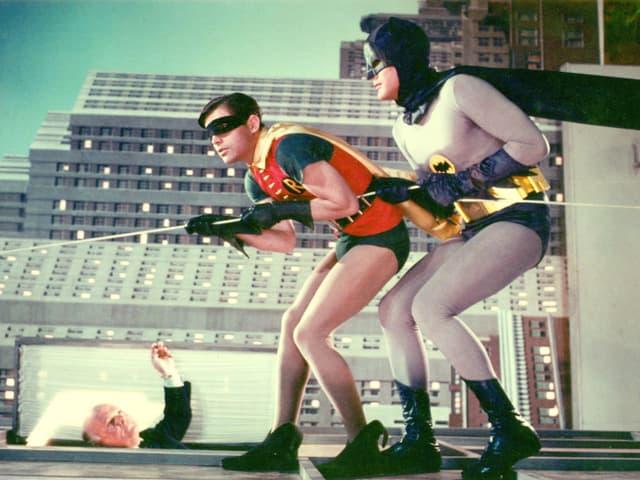 Szene aus der TV-Serie: Batman und Robin, zwei Männer in Superheldenkostümen, klettern an einem Seil eine Gebäudefassade hoch.