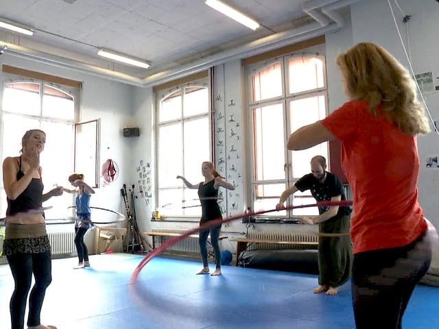 Fabrikhalle mit mehreren Personen in Sportkleidung, die einen Reifen um ihre Hüfte schwingen