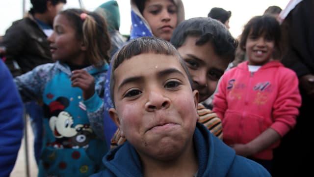 Ein Junge schaut mit aufgewcktem Gesichtsausdruck in die Kamera, hinter ihm weitere Kinder.