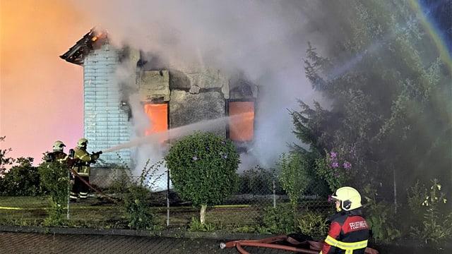 Brennendes, älteres Einfamilienhaus, im Vordergrund Feuerwehrmann