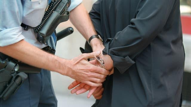 Ein Polizist legt einem Mann Handschellen an.