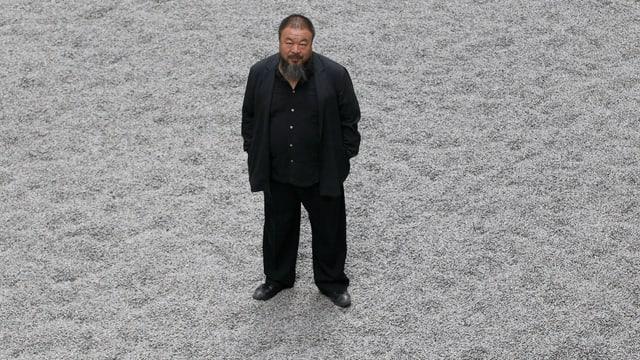 Künstler Ai Weiwei auf grauem Untergrund stehend.