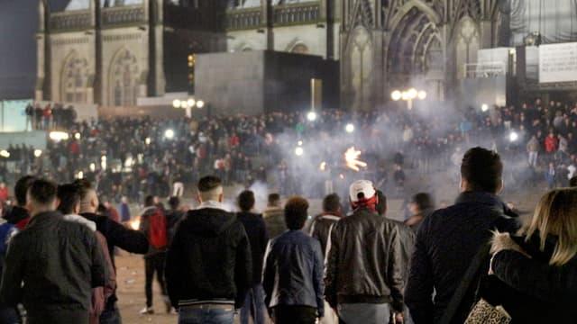 Szene aus der Silvesternacht vor dem Kölner Dom: Viele Junge Männer von hinten aufgenommen, viel Feuerwerk.