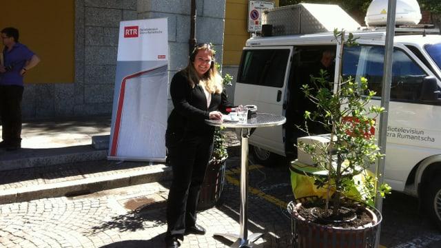 La redactura regiunala Anna Caprez tar la glieud, avant il bus da RTR.