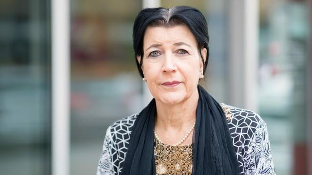 Porträt einer Frau mit dunklen Haaren und Halstuch.