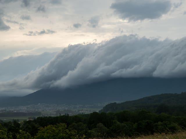 Blick Richtung Jurahügel. Über den Höhen liegen viele graue Wolken. An ihrer Unterseite sind sie wie abgeschnitten.