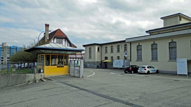 Links ein Wärterhäuschen, rechts das Fabrikgebäude.