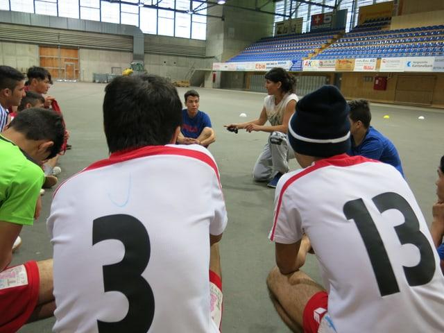 Jugendliche Asylsuchende in einer Sporthallte im Kreis mit der Sportlehrerin.
