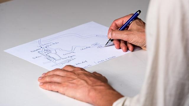 Zwei Hände beim Zeichnen einer Landkarte.