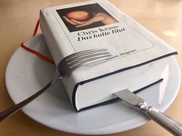 Chris Kraus: «Das kalte Blut» (2017, Diogenes) auf einem Teller