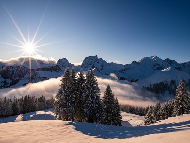 Die Sonne scheint vom blauen Himmel auf eine verschneite Berglandschaft.