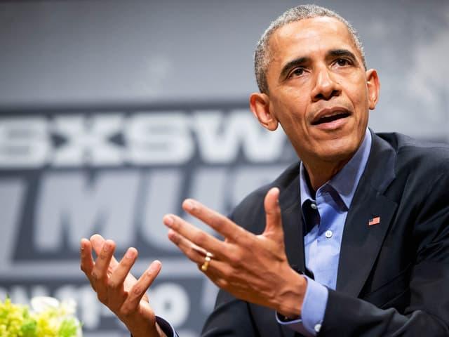 Obama, mit den Händen gestikulierend.