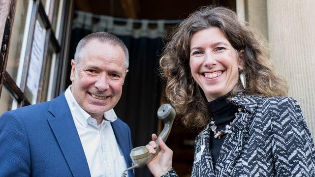 Joachim Salau links und Eva Oertle mit einem alten Telefonhörer vor dem Eingang des Gare du Nord in Basel