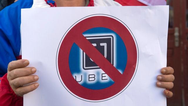 Ein Taxifahrer hält ein Transparent hoch auf dem das Uber-Symbol durchgestrichen ist.