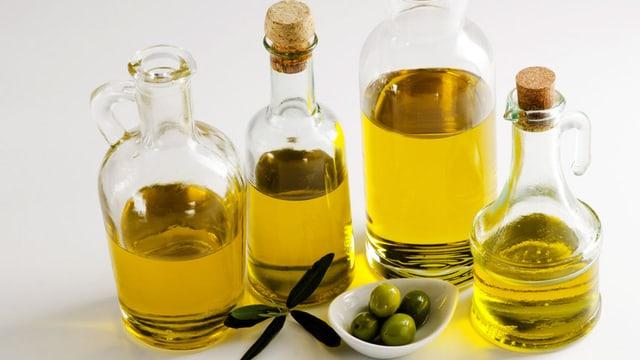 Mehrere Flaschen mit Olivenöl, dazwischen ein Schälchen mit Oliven.